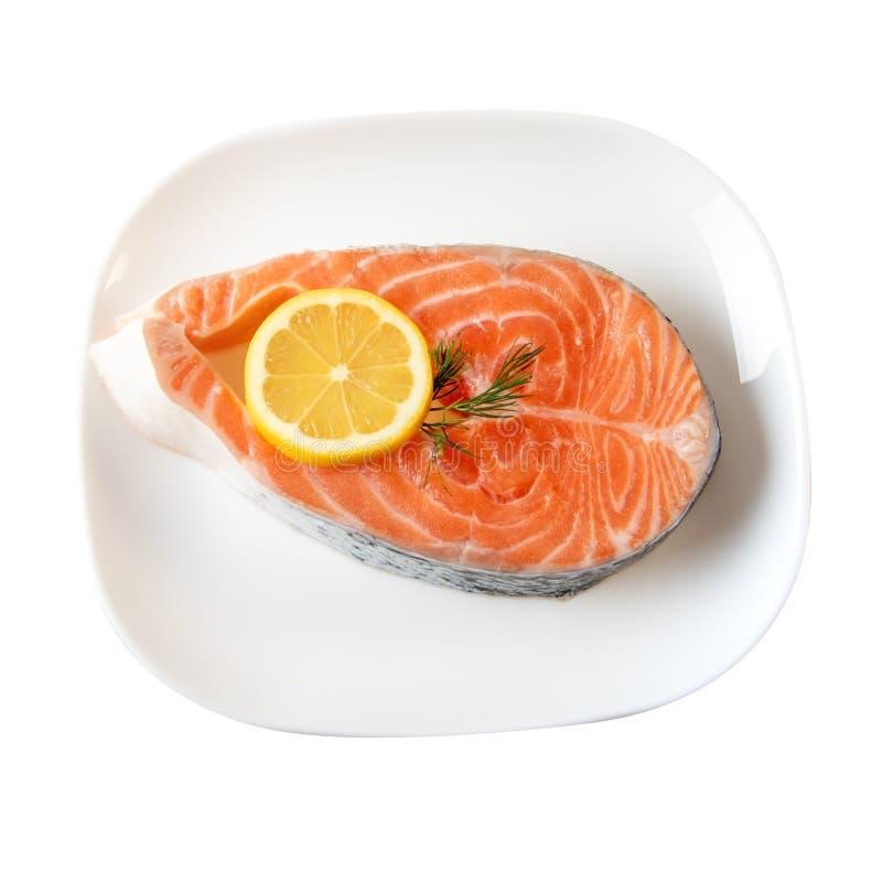 Fresh Salmon Steak On Dinner Plate Wih Lemon Slices Isolated On White stock photo