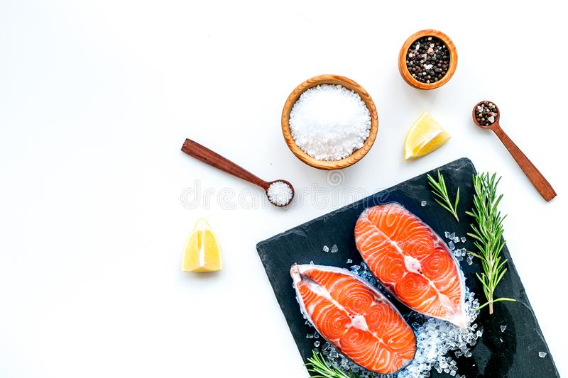 Fresh salmon steak with spices, rosemary, lemon for cooking healthy food on white background top view mock-up royalty free stock images