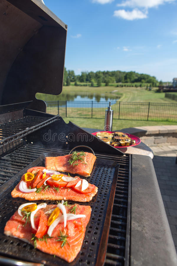 Fresh salmon steaks on the barbecue. Fresh filleted salmon steaks on the barbecue topped with seasoning in the form of onion, tomato and herbs during preparation stock photos