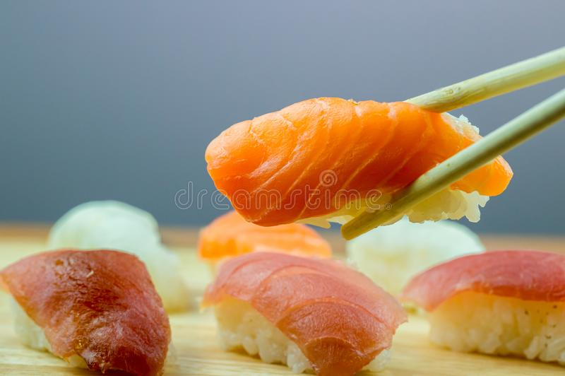Fresh salmon sushi , salmon maki roll Japanese food restaurant, salmon sushi on plate. Sushi platter with a mixed variety of the J. Apanese delicacy at a buffet stock photo