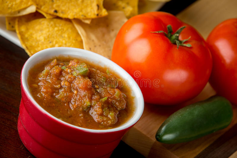 Fresh salsa in red ramekin. Fresh tomato salsa surrounded by ripe tomatoes and jalapeño. In the background is corn chips stock photography