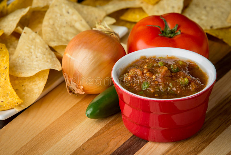 Fresh salsa in red ramekin. Fresh tomato salsa surrounded by ripe tomatoes and jalapeño. In the background is corn chips stock photo