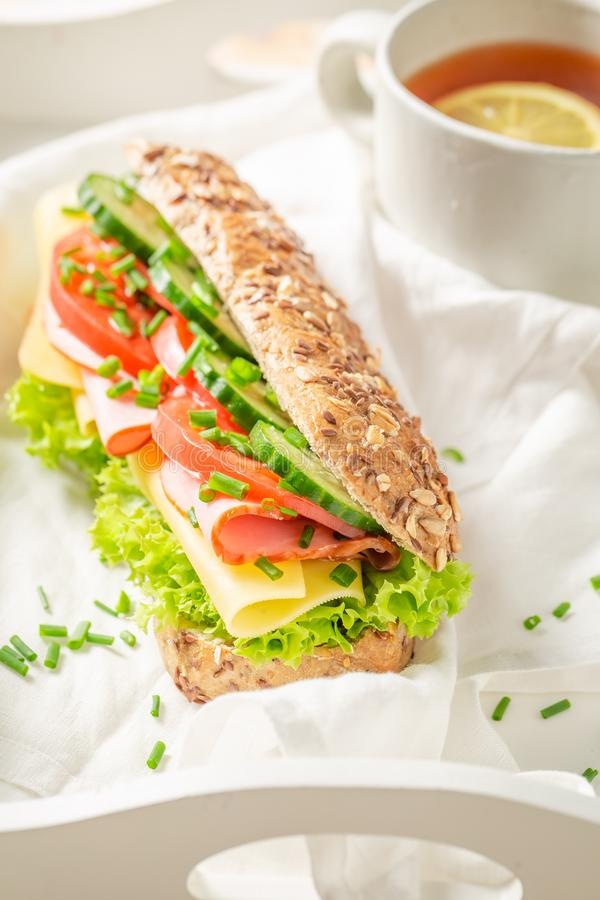 Fresh sandwich with cheese, ham and chive for breakfast. On white table stock images