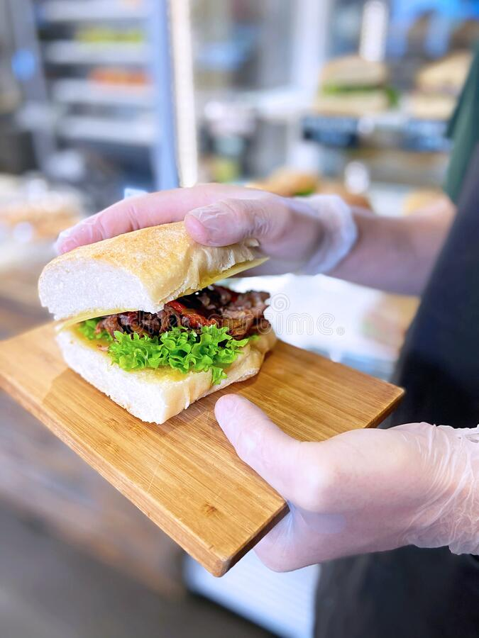 Fresh sandwich cooked on a barbecue lies on the board. Culinary american food for barbecue. Big hamburger with meat steak and stock image