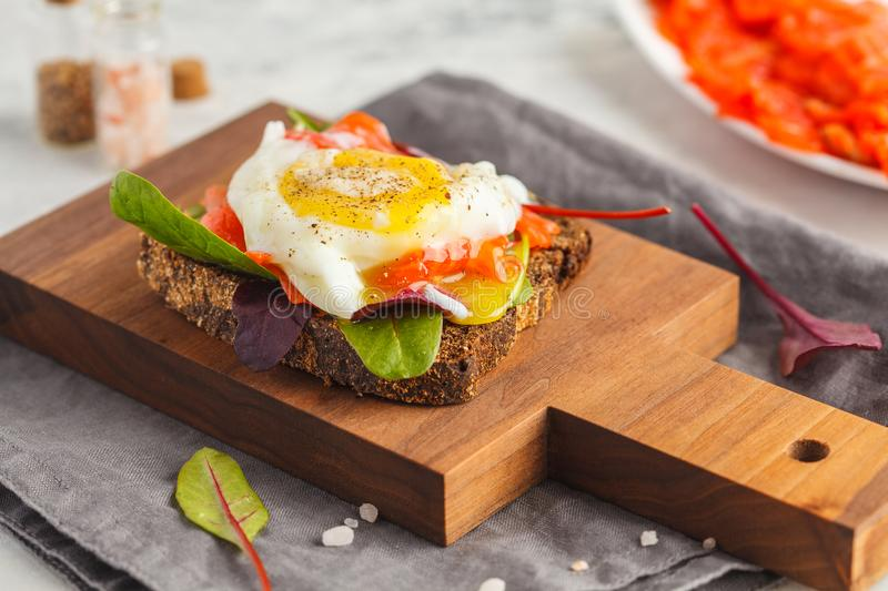Fresh sandwich with egg poached, red fish trout on rye bread. Keto balanced diet food. royalty free stock image