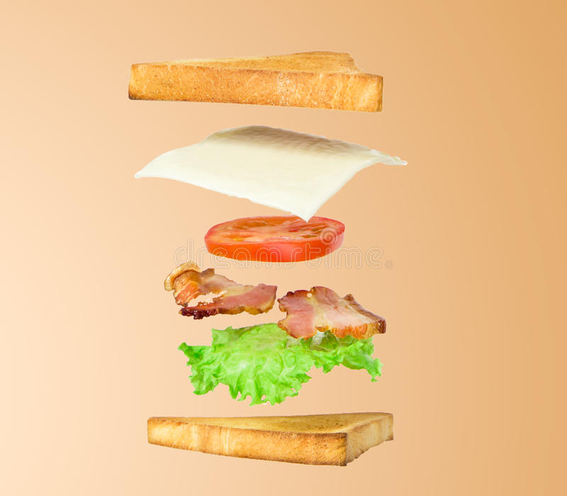 Fresh sandwich with flying ingredients isolated on beige background royalty free stock image