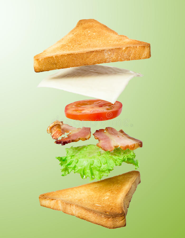 Fresh sandwich with flying ingredients isolated on green background stock photo