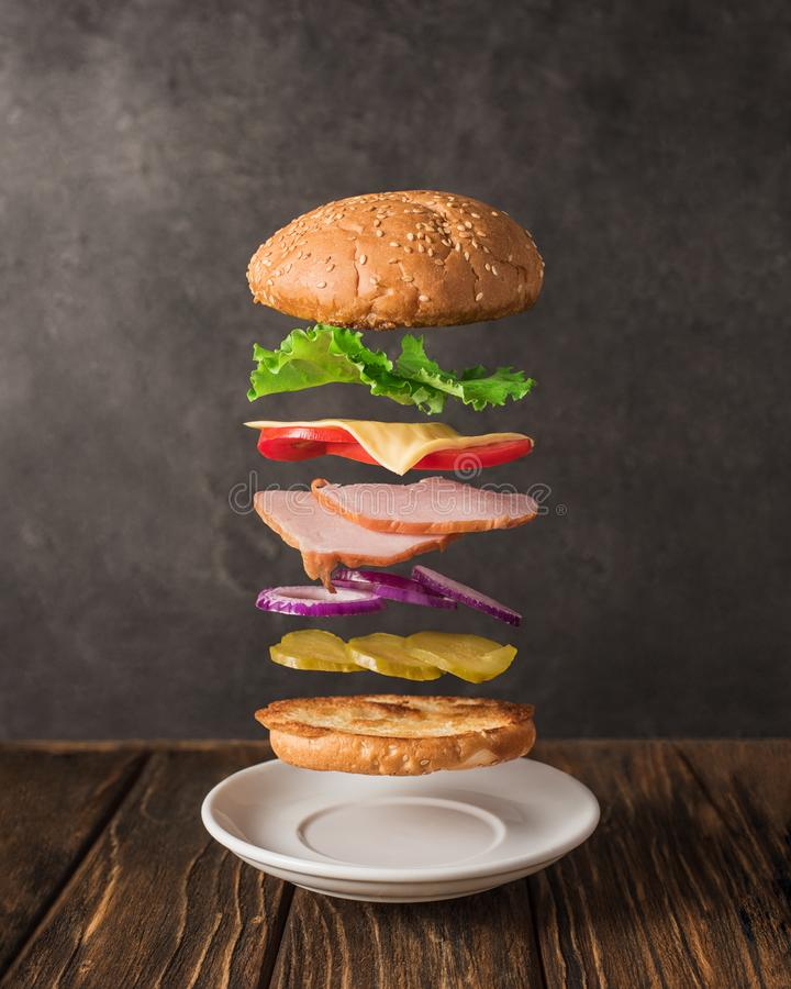 Fresh sandwich with flying ingredients isolated on wooden background royalty free stock photo