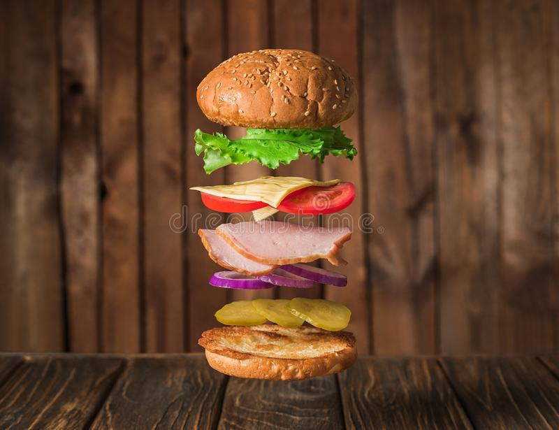 Fresh sandwich with flying ingredients isolated on wooden background stock image