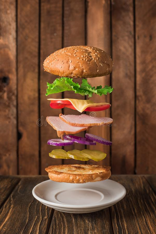 Fresh sandwich with flying ingredients isolated on wooden background royalty free stock images