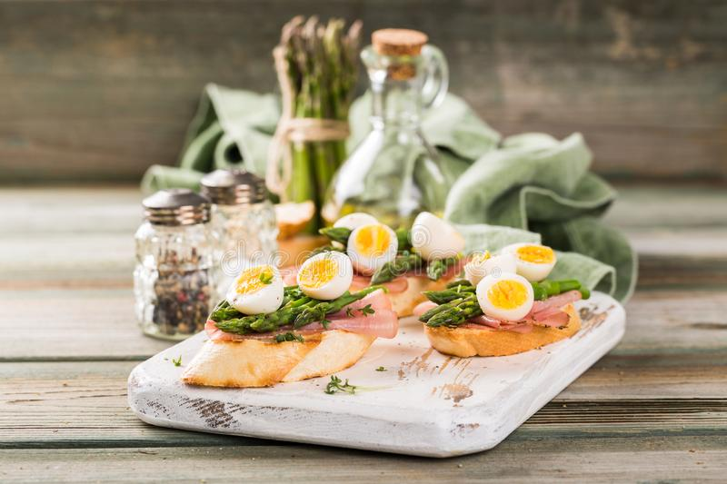 Fresh sandwich with ham, asparagus and quail eggs royalty free stock images