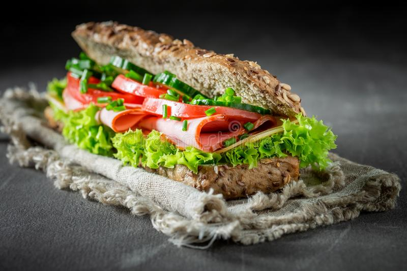 Fresh sandwich with ham, chive and cheese for breakfast. On grey table stock images