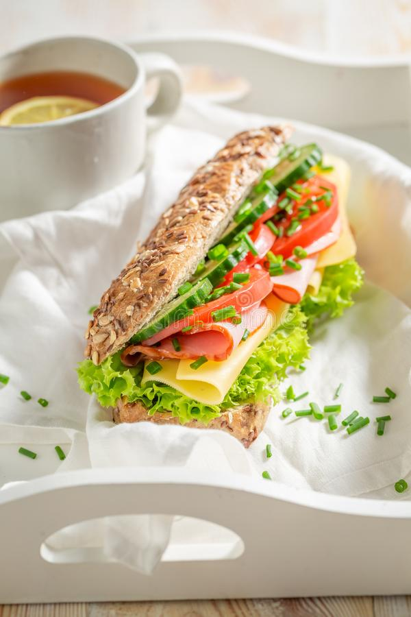 Fresh sandwich with ham, lettue and chive for breakfast. On white table stock photography