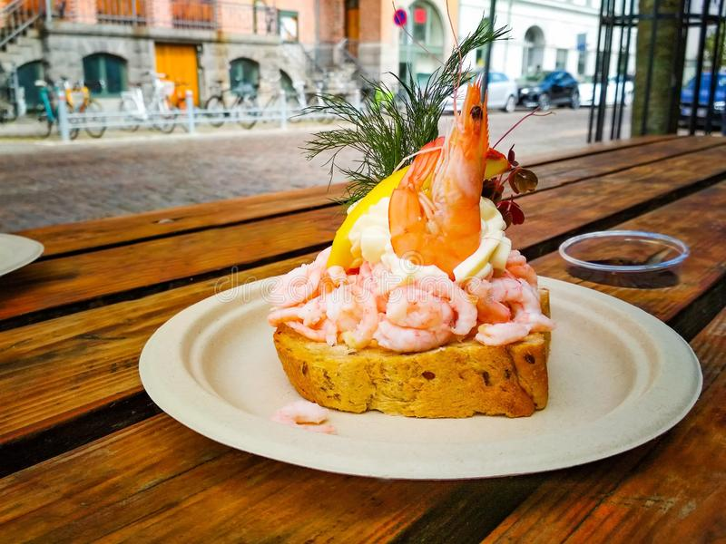 Fresh sandwich with shrimp and lemon in the Danish style, It`s a delicious meal. It is served on a plate on a wooden. Table in Copenhagen. It is summer stock images