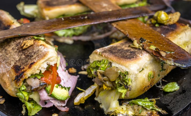 Fresh sandwiches with crispy bread and organic vegetables and cheese and ham and spices are baked on the stove royalty free stock photos