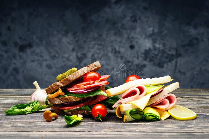 Fresh sandwiches with salami, vegetables, ham and cheese on a wooden table. royalty free stock image