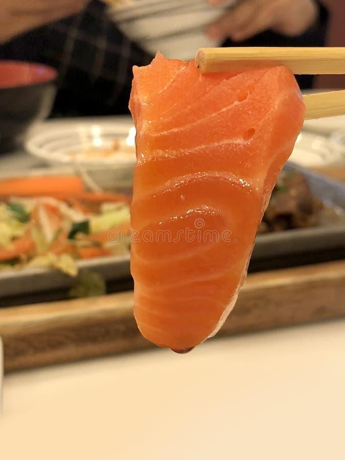 Fresh sashimi salmon with chopsticks on blur background, national food of japan. Fresh sashimi salmon with chopsticks on blur background, national food of japan royalty free stock photography