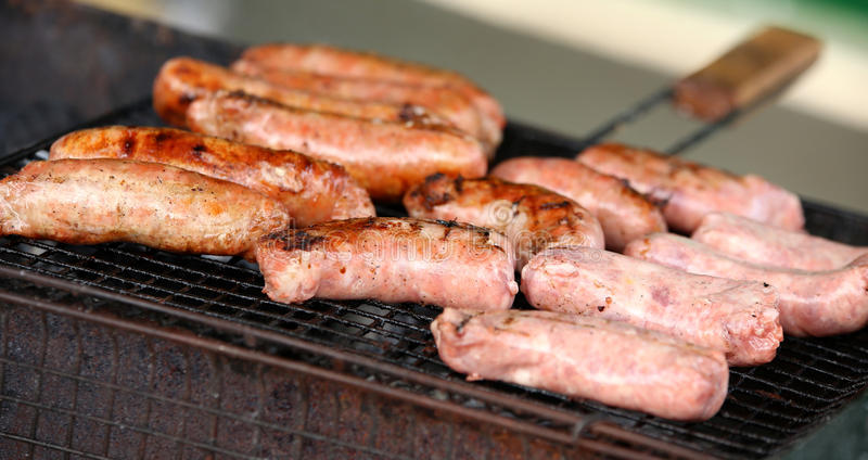Fresh sausage and hot dogs grilling. Fresh sausage and hot dogs grilling outdoors on a barbecue grill stock photography