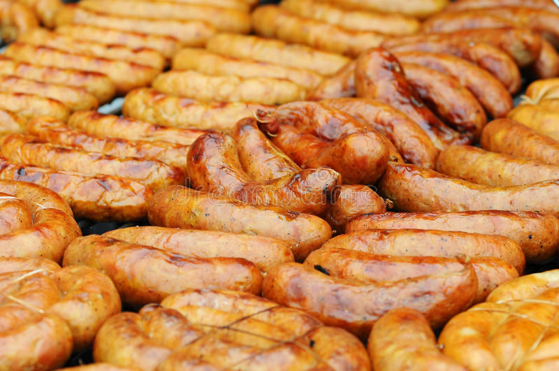 Fresh sausage and hot dogs grilling outdoors on a gas barbecue grill. Closeup of sausage on the grill.  royalty free stock image