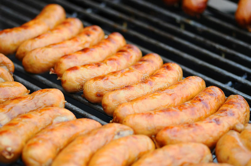 Fresh sausage and hot dogs grilling outdoors on a gas barbecue grill. Closeup of sausage on the grill.  royalty free stock photo