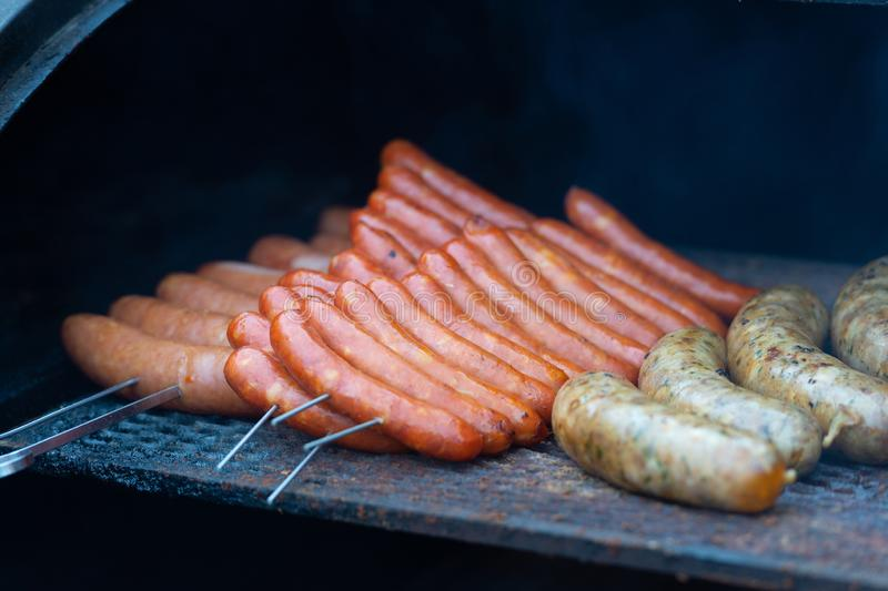 Fresh sausage and hot dogs grilling outdoors stock photos