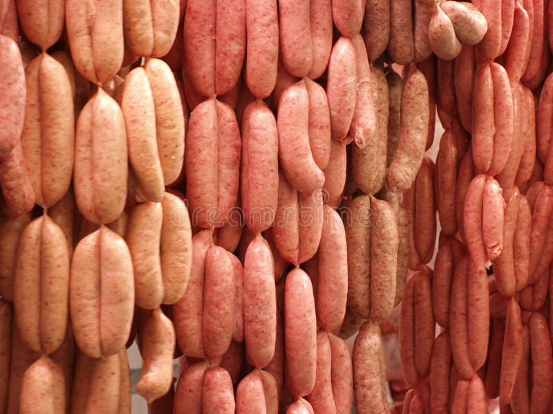 Fresh sausages hanging on hooks stock photography