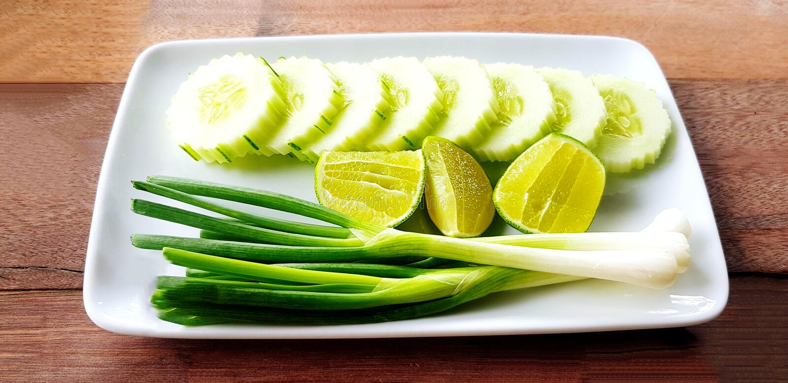 Fresh Scallion, sliced cucumber and lime or lemon in white plate on wooden table. Organic vegetable food and Harvest of agriculture concept stock photo