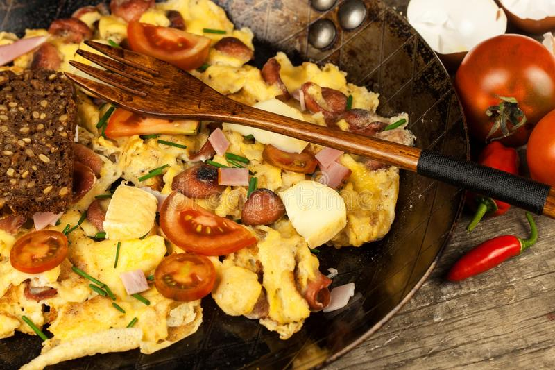 Fresh scrambled egg with ham and chilli peppers on a steel pan. A nourishing traditional breakfast. Calorie meals. Fresh scrambled egg with ham and chilli stock photo