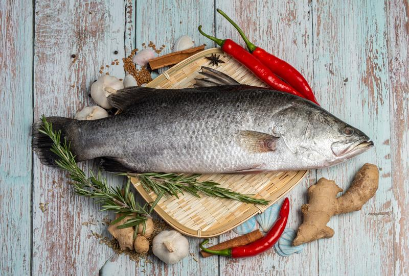Fresh Sea Bass on rattan plate and wooden background. Fresh Sea Bass on wooden table surrounded by spices royalty free stock images