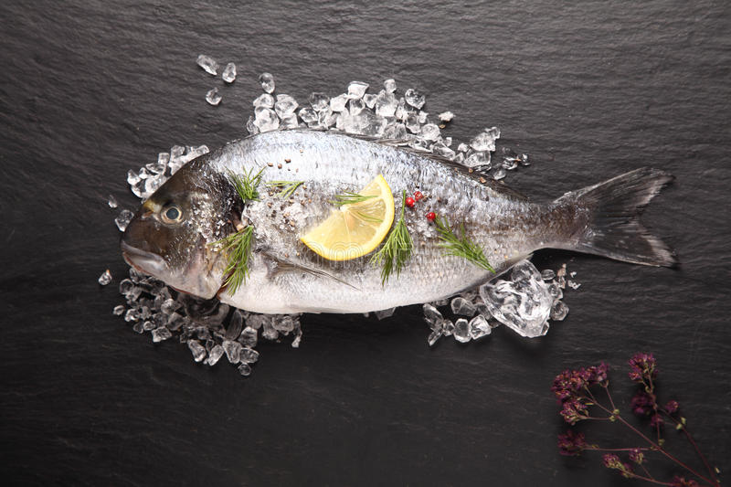 Fresh sea bream cooling on crushed ice. Fresh sea bream or dorade cooling on crushed ice with lemon and herbs waiting to be cooked for a delicious seafood dinner stock images