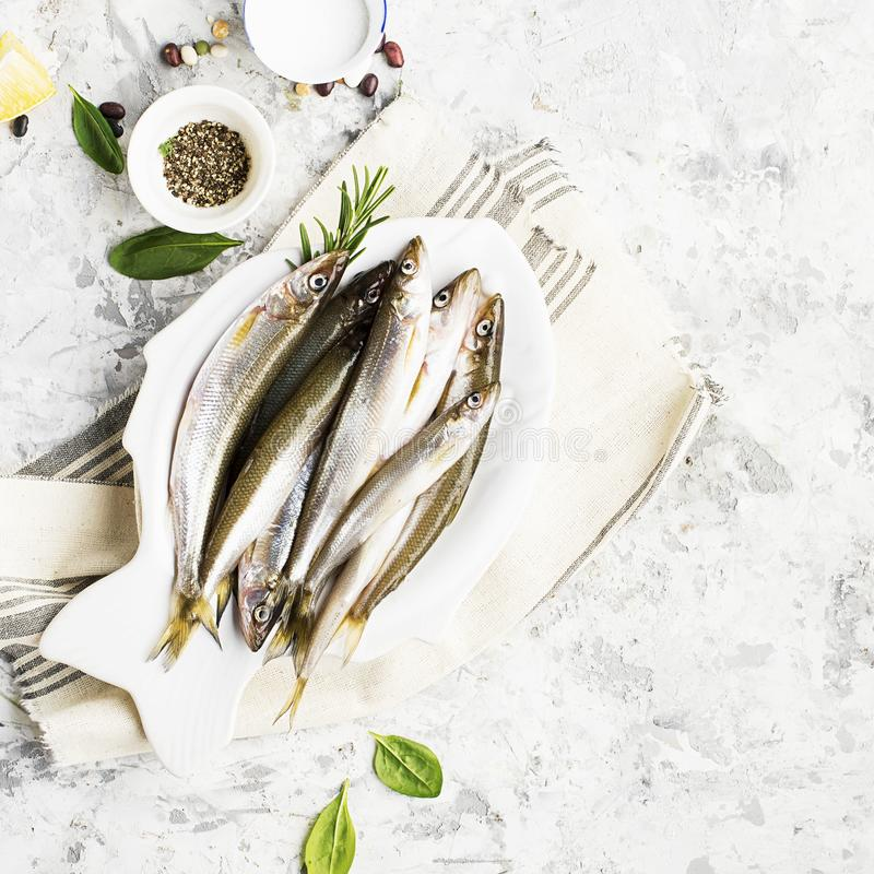 Fresh sea cold-water small fish such as smelt, sardine, anchovies on a simple background with fresh spinach, lemon stock photography