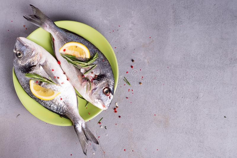 Fresh sea fish with spices and lemon ready for cooking on plate. Dorado or sea bream fish on stone background. Flat lay. Fresh uncooked dorado or sea bream fish royalty free stock photos