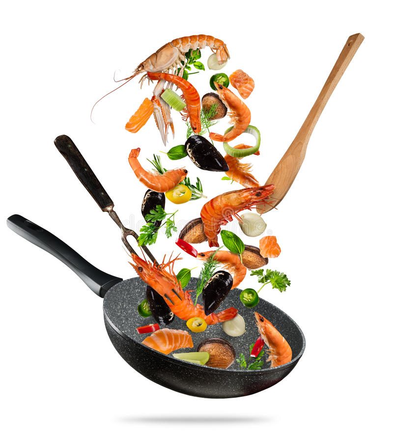 Fresh sea food and vegetables flying into a pan on white background stock image
