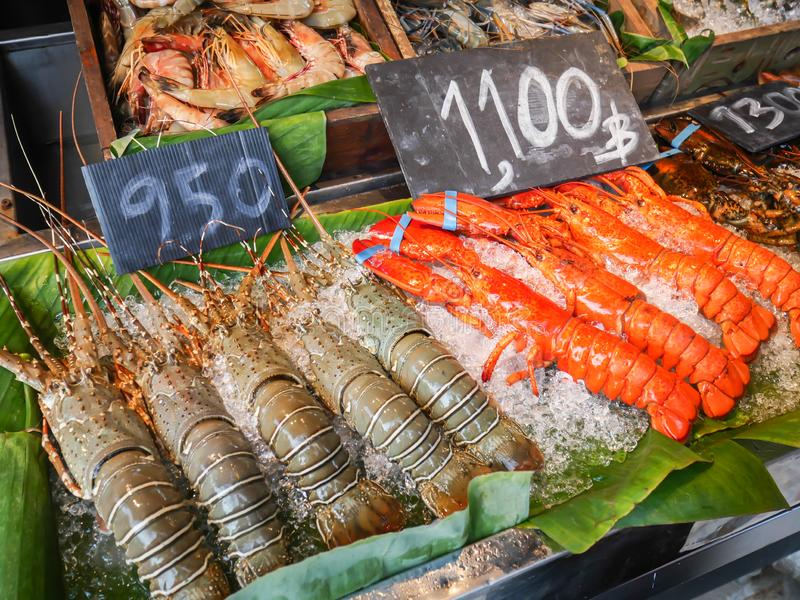 Fresh seafood arrangement displayed on the ice shelf. For sale on the night street market in hua hin, Thailand. With price tag stock image