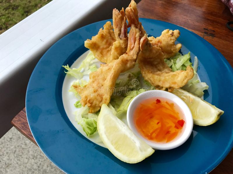 Fresh seafood in a blue plate. Tiger prawn tempura with salad royalty free stock image
