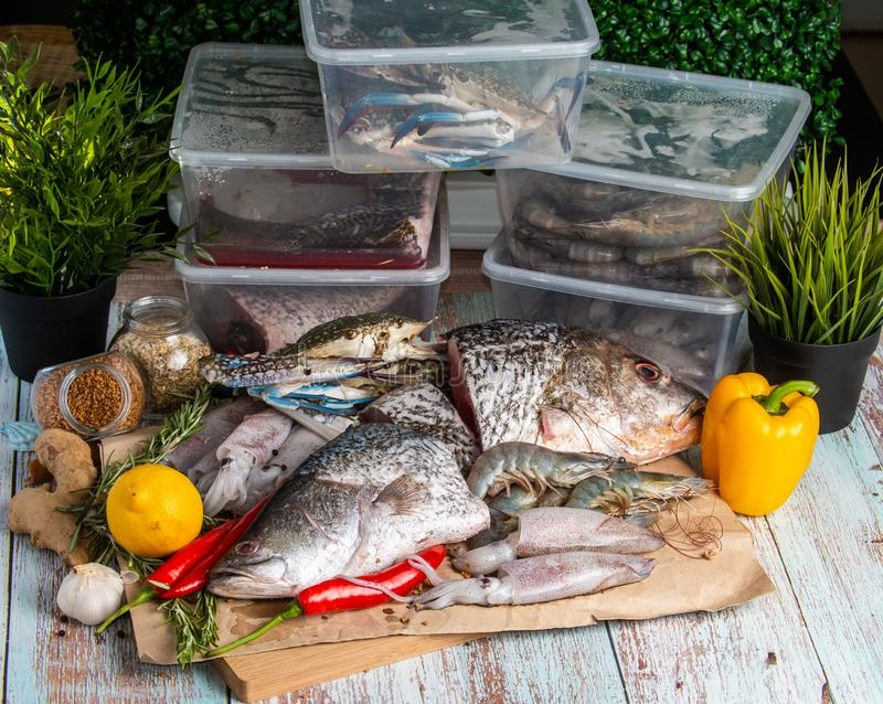 Fresh Seafood - Golden Snapper, Sea Bass, Prawns, Crabs, and Squids. Fresh Seafood - Golden Snapper, Sea Bass, Prawns, Crabs, and Squids - on a wooden table royalty free stock image