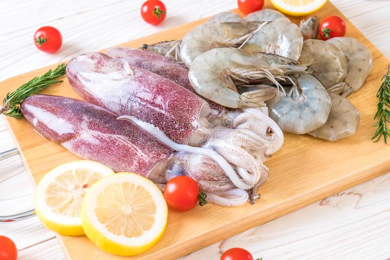 fresh seafood raw (shrimps ,squids) on wooden board royalty free stock photos