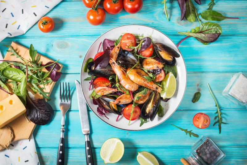 Fresh seafood salad, mussels, shrimp, fresh vegetables and herbs on blue wooden table royalty free stock images