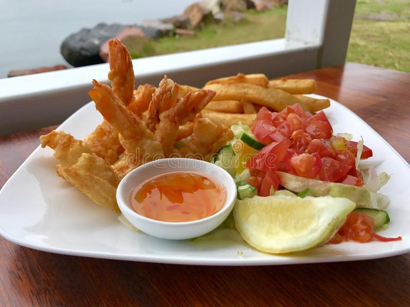 Fresh seafood. Tiger prawn tempura with chips and salad stock image
