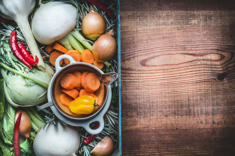 Fresh seasonal organic local vegetables box for healthy clean eating and cooking on rustic wooden background, top view, place for stock photos
