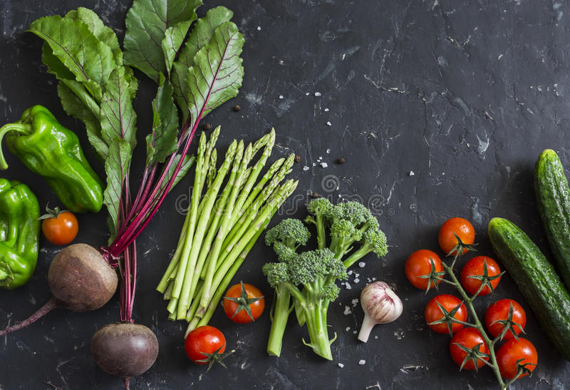 Fresh seasonal vegetables - beetroot, asparagus, broccoli, tomatoes, peppers, cucumbers on a dark background. Healthy food concept. Flat lay royalty free stock image