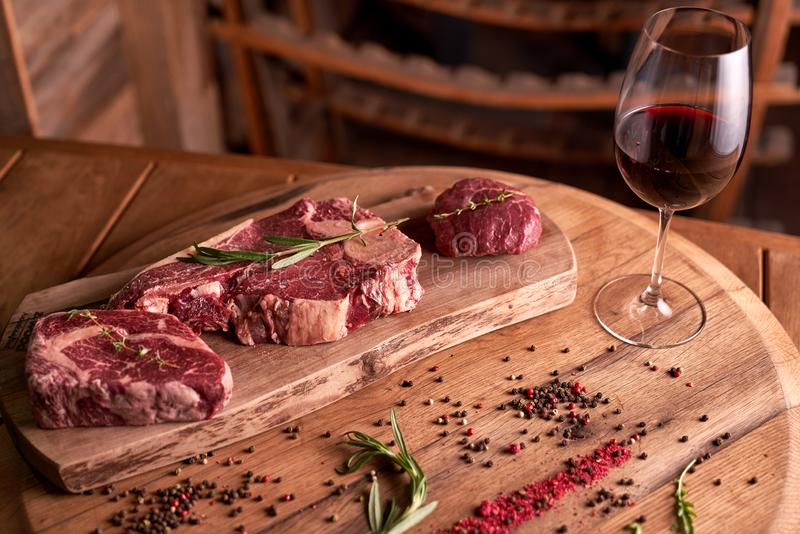 A fresh, seasoned Ribeye steak on a cutting board with pepper, rosemary. Near a glass of red wine stock photo