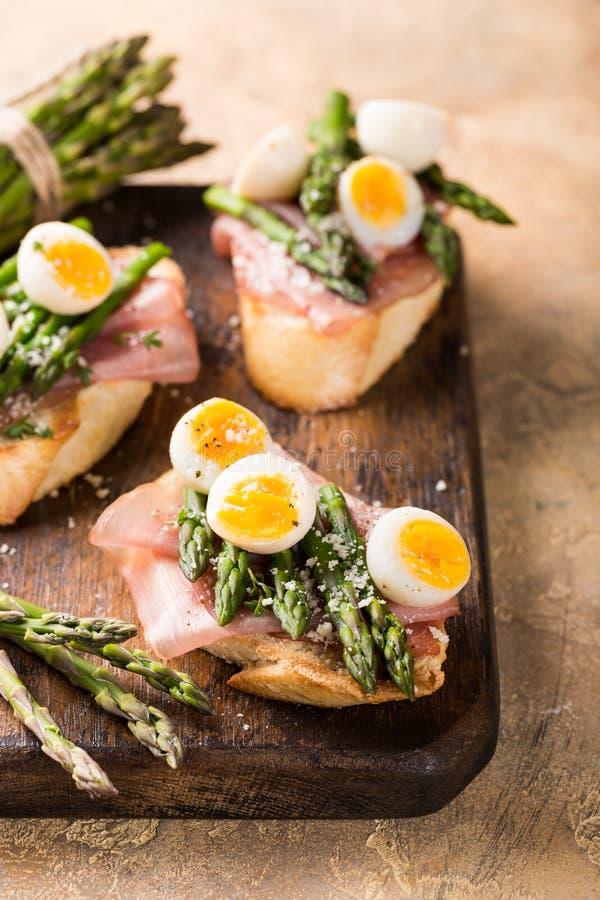 Fresh sendwich with ham, asparagus and quail eggs stock images