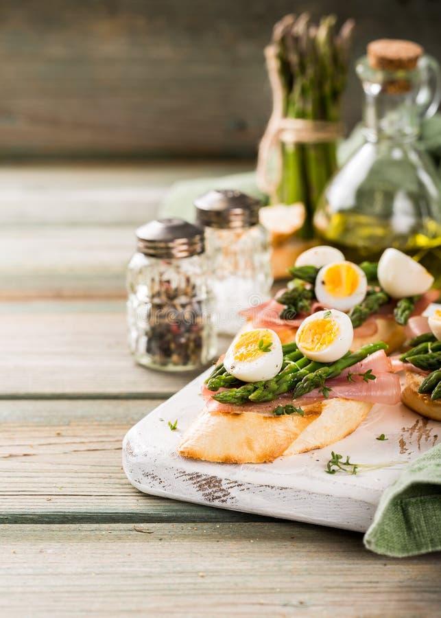 Fresh sendwich with ham, asparagus and quail eggs royalty free stock photo