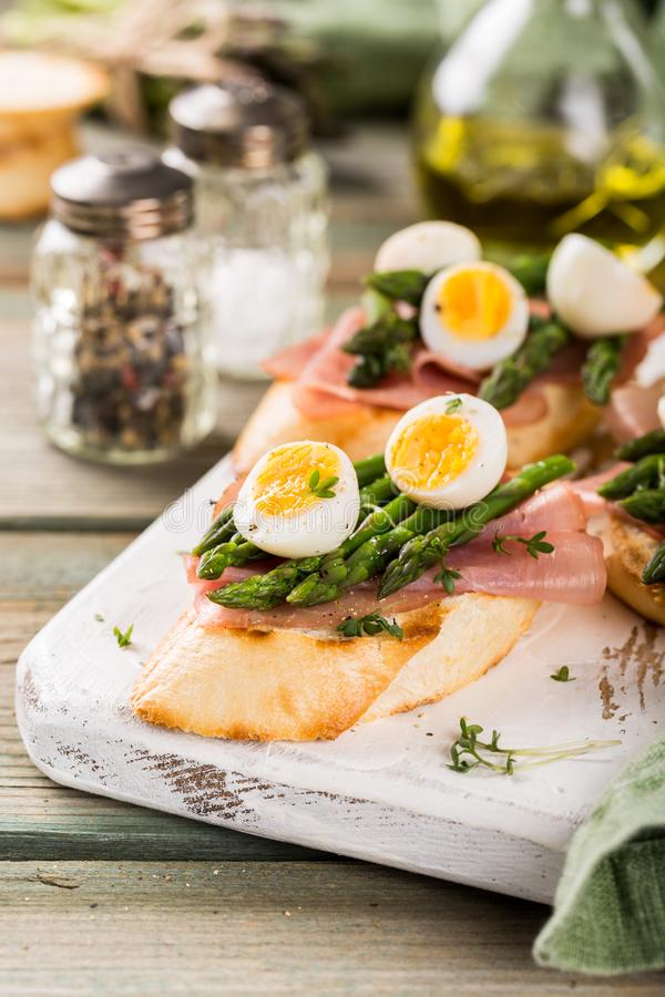 Fresh sendwich with ham, asparagus and quail eggs royalty free stock photography