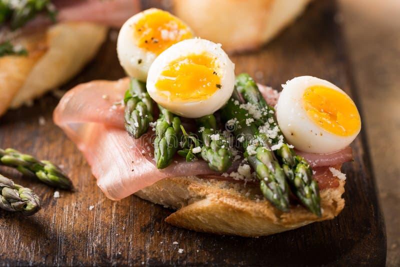 Fresh sendwich with ham, asparagus and quail eggs stock photos