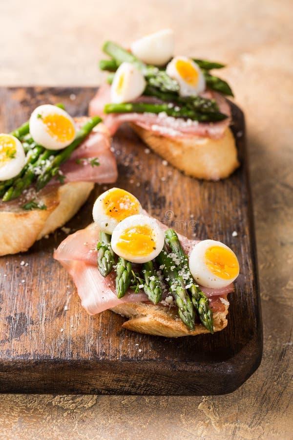 Fresh sendwich with ham, asparagus and quail eggs stock photo