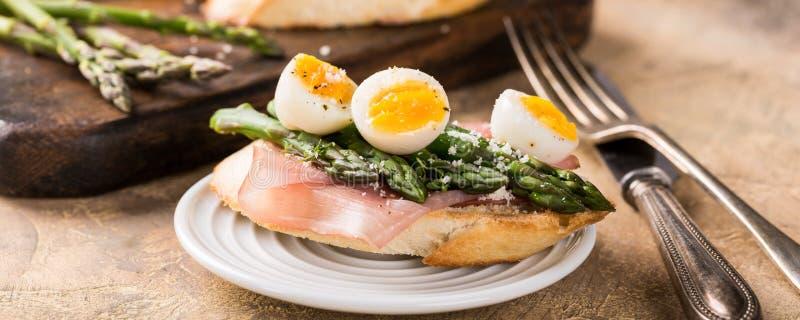 Fresh sendwich with ham, asparagus and quail eggs stock photography