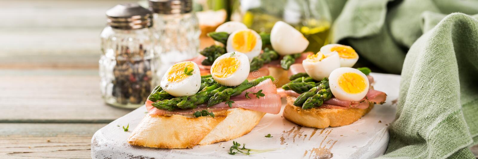 Fresh sendwich with ham, asparagus and quail eggs royalty free stock image