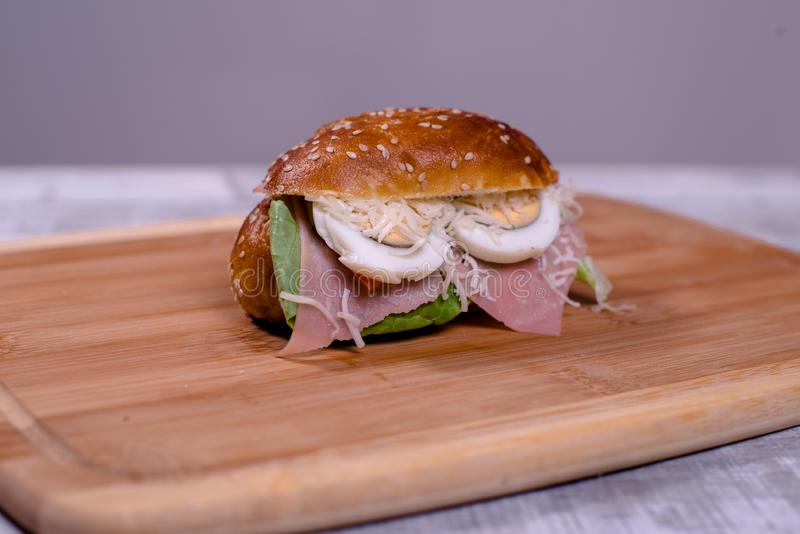 Fresh sendwich with ham, lettuce, quail eggs, cheese and tomatoes royalty free stock photography